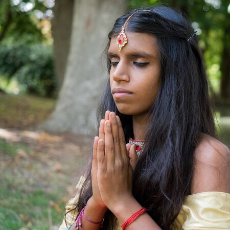 hinduism: Beautiful young indian woman praying in the park. Hinduism | religion | spirituality concept