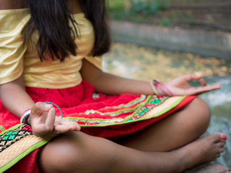 Hindu woman meditating in the park in Yoga posture with mudra (hands position)