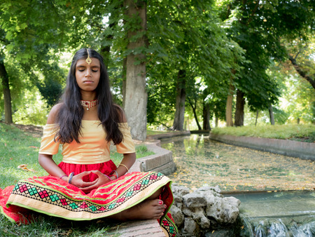 hinduism: Beautiful young indian woman practicing meditation in the park. Hinduism religion. Radja Yoga practice