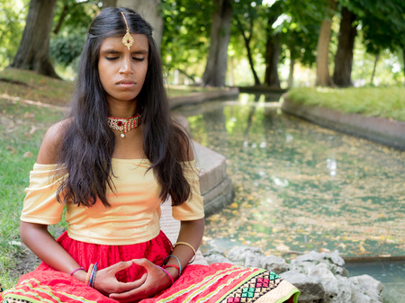conscience: Beautiful young indian woman practicing meditation in the park. Hinduism religion. Radja Yoga practice
