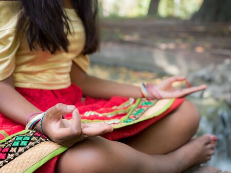 conscience: Hindu woman meditating in the park in Yoga posture with mudra (hands position)