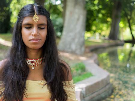 hinduismo: Feliz joven y bella mujer india práctica de la meditación en el parque. mindfullness concepto. la religión del hinduismo. La práctica del yoga radja