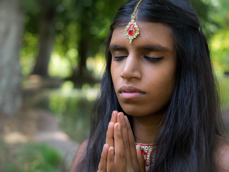 hinduismo: Beautiful young indian woman praying in the park. Hinduism | religion | spirituality concept