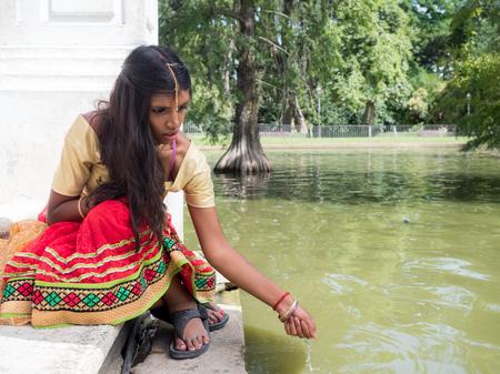 melancholy: Beautiful and melancholic young indian woman sitting at the lake side. Melancholy concept