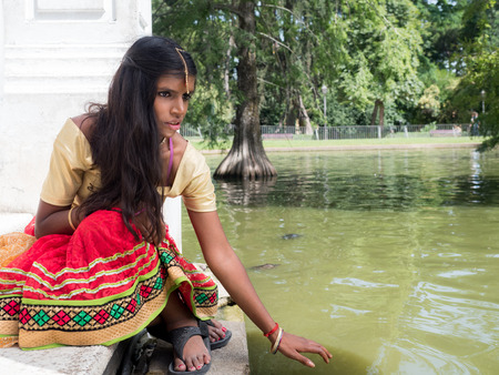 melancholy: Beautiful young indian woman with nice eyes sitting at the lake shore. Melancholy concept
