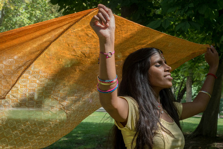 tribal park: Happy indian beautiful young woman dancing in the park. Happiness and enjoying the present moment (here  and now) concept;