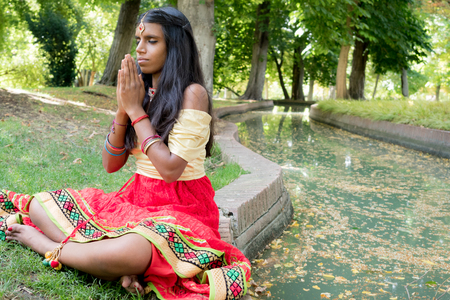 hinduism: Beautiful young indian woman praying and meditating in the park. Hinduism religion. Radja Yoga practice Stock Photo