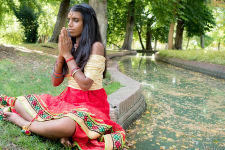 hinduismo: Hermosa joven India orando y meditando en el parque. la religión del hinduismo. La práctica del yoga radja