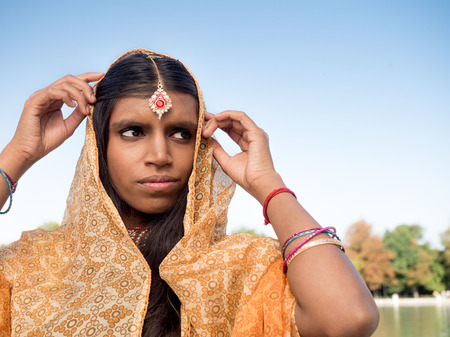 sari: Beautiful and traditional young indian woman putting on a sari