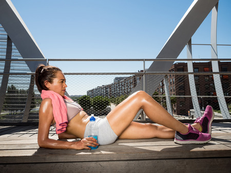 hydration: Female runner relaxed lying and resting after making a big effort. Recovery and hydration concept Stock Photo