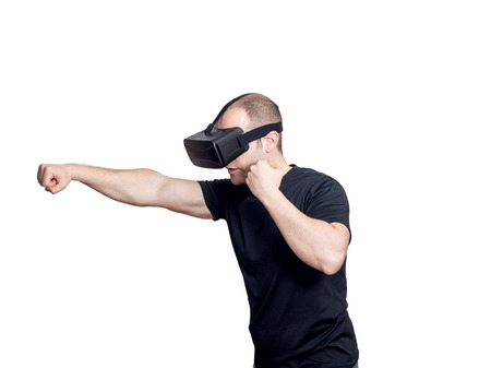 Man with virtual reality headset playing a sport fight video game isolated on white background. Entertainment and gaming technology concept. Stock Photo