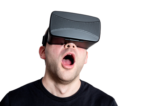 entertainment background: Amazed man using virtual reality glasses isolated on white background. Technology immersion concept.