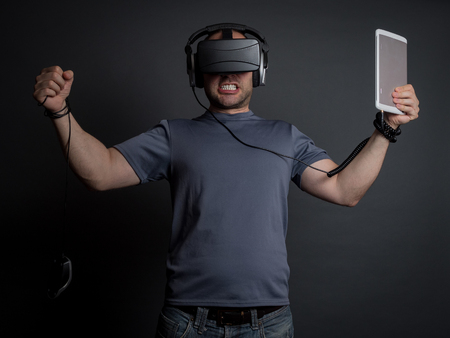 obsessed: Addicted man to technology, virtual reality and video games going crazy. Modern addictions concept.