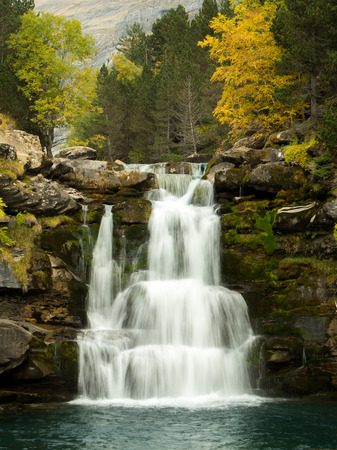 Waterfall in the forest in the mountains in autumn