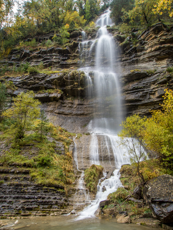 ordesa: Waterfall and trees in a cliff in autumn Stock Photo