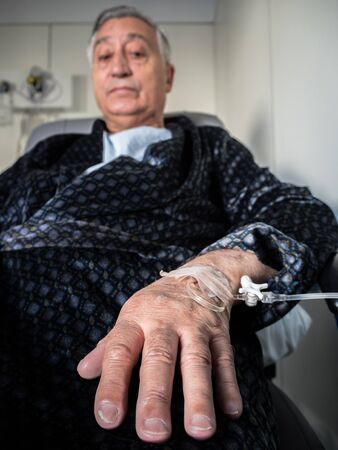 iv: Old patient man with iv drip in the hand. Hand close-up detail
