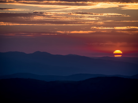 Sunrise over mountains with twilight sky with big contrast between warm and cold colors