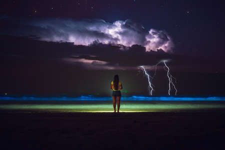 Girl with her back with a thunderstorm facing the sea and plankton at night