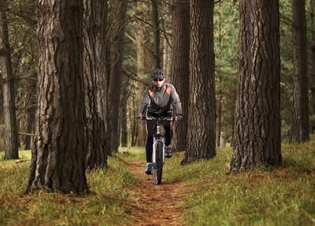 Man practicing mountain biking in the forest looking at the cameraHombre practicando mountain bike en el bosque mirando a la c�mara Stock Photo