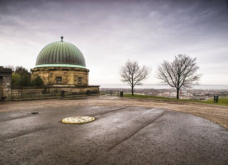 dome building: Dome building and Calton Hill, Edinburgh  There are two leafless trees and the sky is overcast  Stock Photo