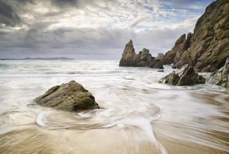 Plage avec de l'eau et les roches La photo a été prise sur une plage en Galice, Espagne