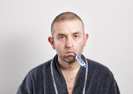 Sick man with thermometer on white background rA normal man, no model  photo