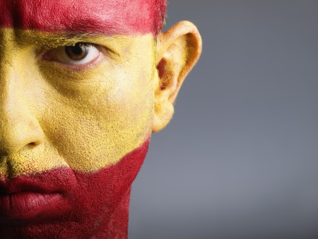 Man with his face painted with the flag of Spain  The man is seus and photographic composition leaves only half of the face  Stock Photo - 13236940