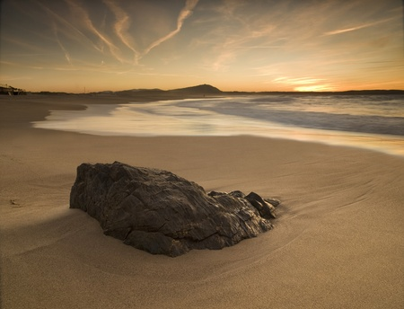 Sunset on the beach with rock in the foreground The photo is taken in Valdoviño, Galicia, Spain Stock Photo
