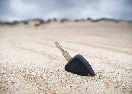 Car key lost in the sand on the beach Standard-Bild