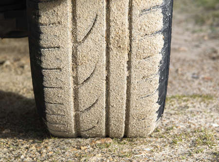 grooves: Car wheel stuck in sand, the sand is stuck in the grooves of the wheel