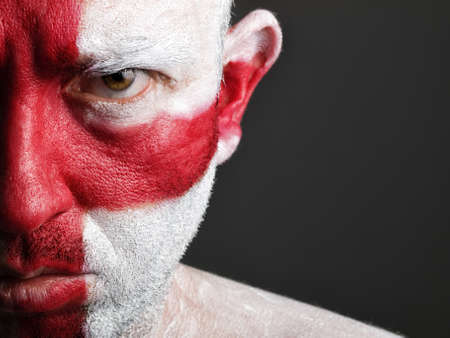 Man with his face painted with the flag of England.  The man is serious and photographic composition leaves only half of the face. photo