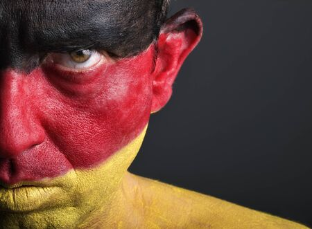Man with his face painted with the flag of Germany.  The man is serious and photographic composition leaves only half of the face. photo