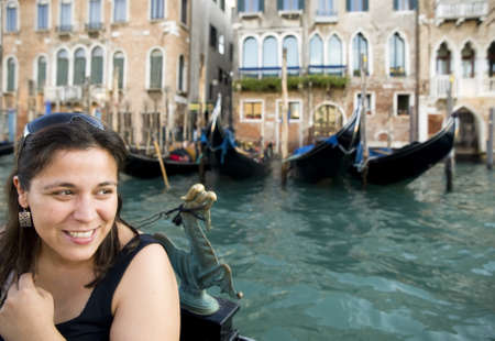 expresses: Happy woman with gondola in Venice. She looks to the side and expresses positive