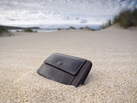 Billfold on the beach over the sand photo
