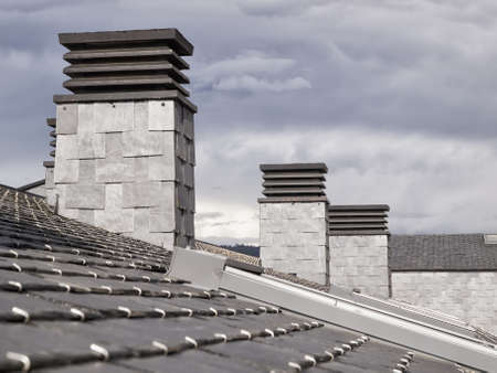 fireplaces: Three fireplaces on a slate roof in a cloudy day.  Stock Photo