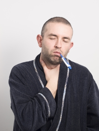 sore throat: Sick man with his eyes closed. The man has a thermometer in his mouth and sore throat Stock Photo