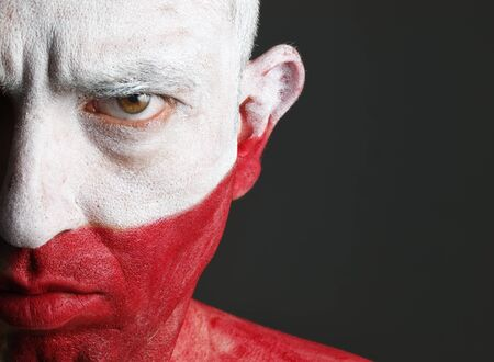 Man with his face painted with the flag of Poland.  The man is serious and photographic composition leaves only half of the face. Stock Photo
