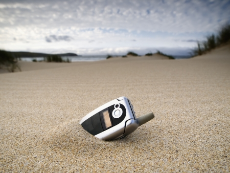 forgotten: forgotten mobile phone on the beach and over the sand Stock Photo