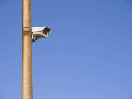 Video surveillance camera attached to a metal pole and blue sky background photo