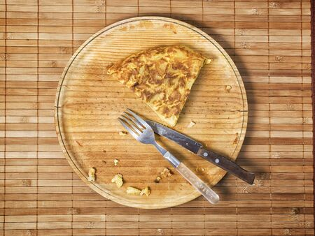 leftover: food scraps, Spanish omelette on a plate of wood with a knife and fork Stock Photo