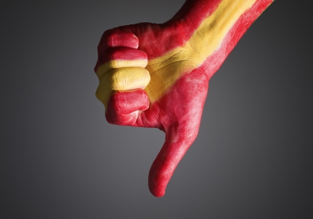 expressing negativity: Hand painted with the flag of Spain and expressing negativity and isolated on dark background Stock Photo