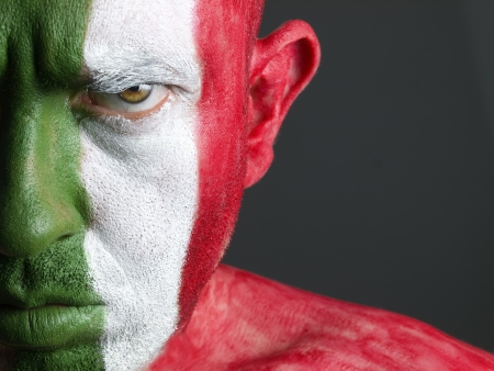 Man with his face painted with the flag of Italy. The man is serious and photographic composition leaves only half of the face.