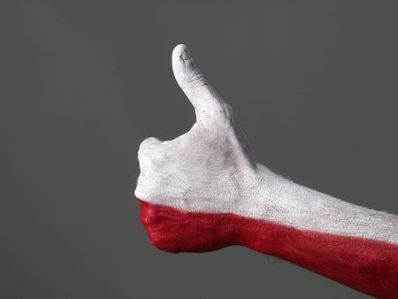 positivity: Hand painted with the flag of Poland and expressing positivity and isolated on dark background Stock Photo