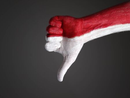 expressing negativity: Hand painted with the flag of Poland and expressing negativity and isolated on dark background Stock Photo