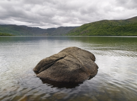 zamora: A lake with a rock in the middle  The photo is taken in the Sanabria lake, Zamora, Spain  Stock Photo