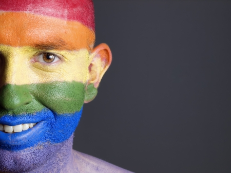 flag painted on the face of a man. Man is looking at camera and is smiling photo