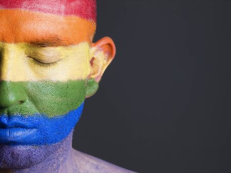 flag painted on the face of a man.The mans eyes are closed with a serene expression on his face photo