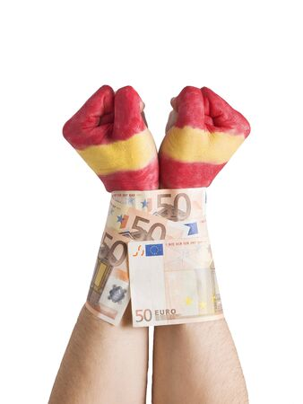 Two hands painted flag Spain and cuffed with 50 euro notes. The picture is intended to convey the concept of the spanish economic crisis we are experiencing the pressure as well as markets and banks over Spain and its people. photo