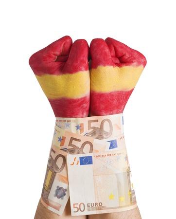 crisis economica: Dos manos pintadas bandera de Espa�a y esposado con billetes de 50 euros. La imagen se pretende transmitir el concepto de la crisis econ�mica espa�ola que est�n experimentando la presi�n, as� como los mercados y los bancos de Espa�a y su gente.