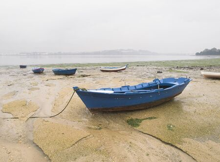 Set of boats stranded on the sand at low tide. The picture was taken in Ferrol, Galicia, Spain.